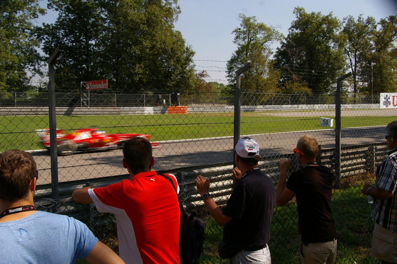 Zuschauer vor Zaun und Formel 1 Auto im Hintergrund