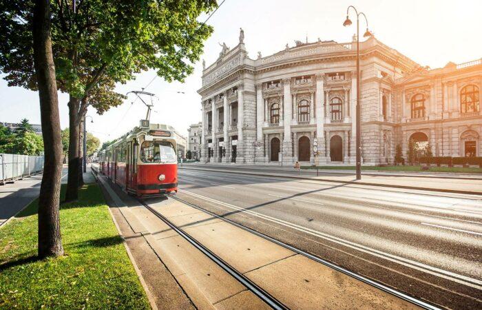 Rote Strassenbahn mit historischem Gebäude im Hintergrund