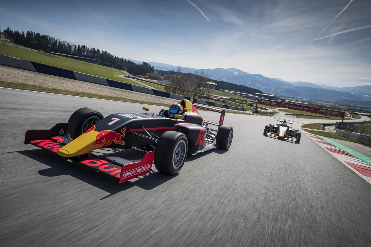 Formel Auto auf Rennstrecke mit Bergen im Hintergrund